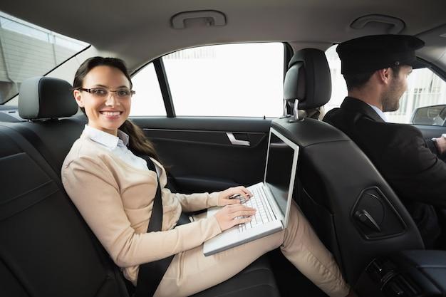 Jeune femme d'affaires étant chauffeur tout en travaillant Photo Premium
