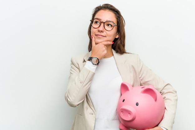 Jeune femme d'affaires européenne tenant une tirelire à la recherche de côté avec une expression douteuse et sceptique. Photo Premium