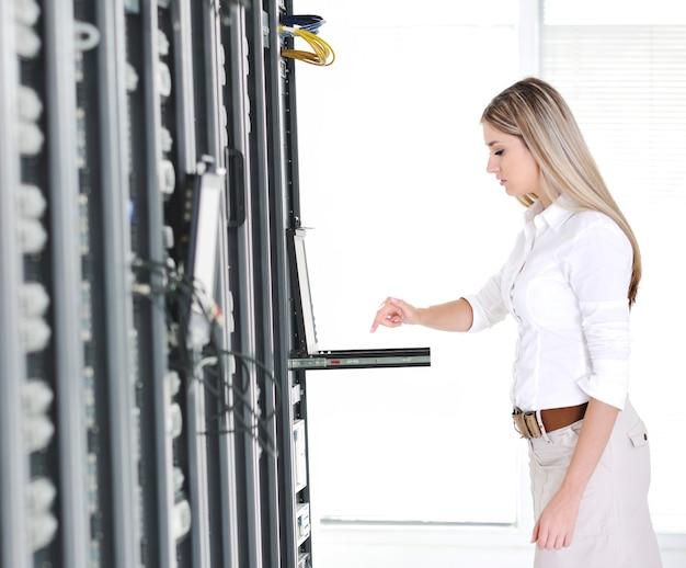Jeune femme d'affaires féminin avec ordinateur portable moderne dans la salle des serveurs réseau Photo Premium