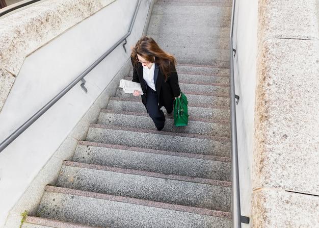 Jeune, femme affaires, journal, sac, monter escalier Photo gratuit