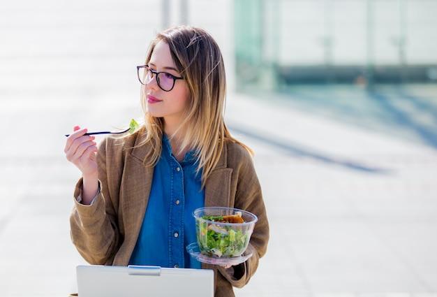 Jeune femme d'affaires, manger de la salade et travaillant avec l'ordinateur en plein air Photo Premium