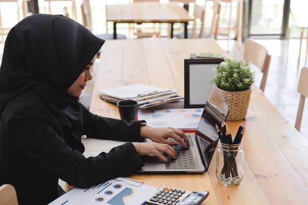 Jeune femme d'affaires musulmane portant un hijab noir, travaillant au coworking. Photo Premium
