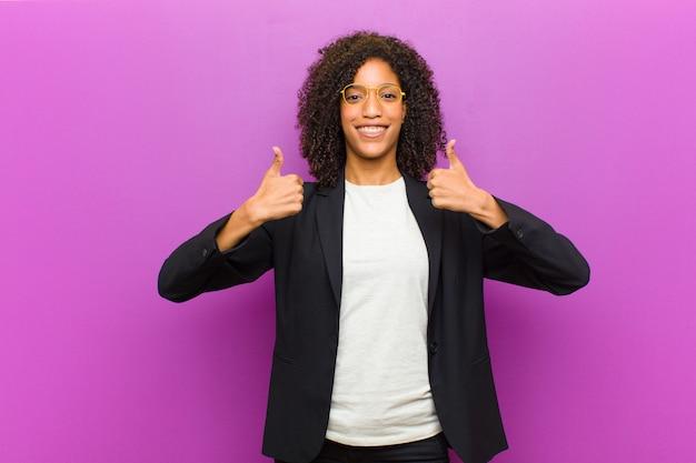 Jeune femme d'affaires noire souriante regardant largement heureux, positif, confiant et réussi, avec les deux pouces Photo Premium