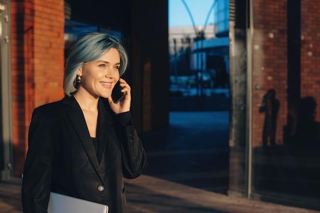 Jeune Femme D'affaires Parlant Au Téléphone Et Sourire En Marchant Avec Un Ordinateur Photo Premium