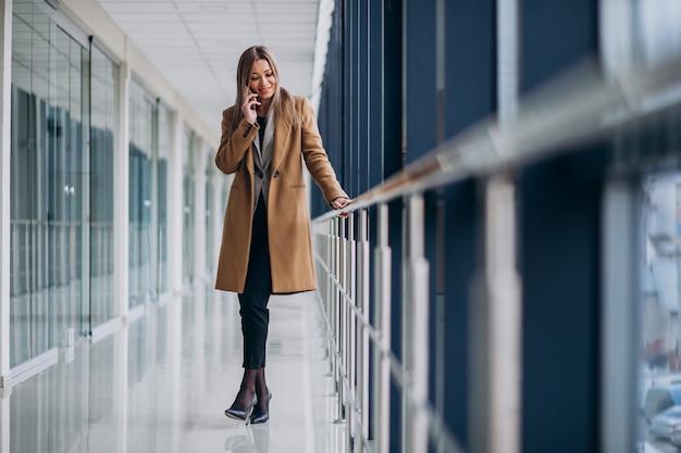 Jeune Femme D'affaires, Parler Au Téléphone Dans Un Aéroport Photo gratuit