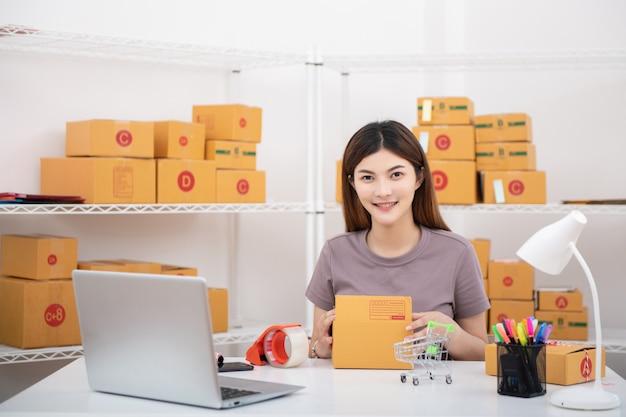 Jeune femme d'affaires de propriétaire adolescent asiatique travaille à la maison pour faire des achats en ligne Photo Premium