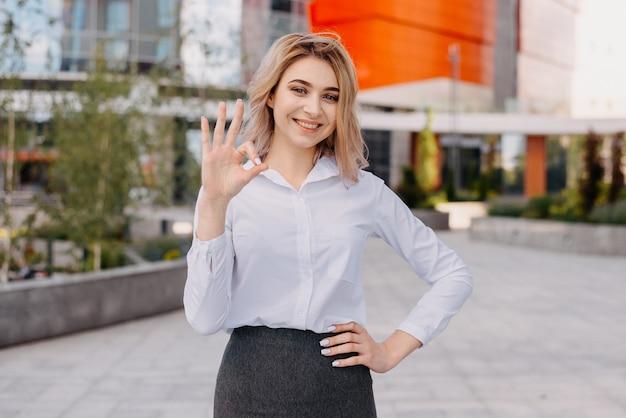 Une Jeune Femme D'affaires Prospère à Côté D'immeubles Commerciaux Modernes De Plusieurs étages Immeuble De Bureaux Rouge Photo Premium