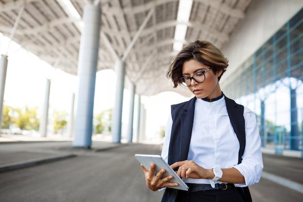 Jeune Femme D'affaires Prospère, Regardant La Tablette, Debout Près Du Centre D'affaires. Photo gratuit