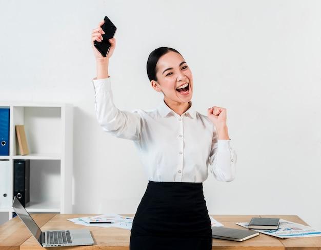Jeune femme d'affaires réussie tenant mobile dans la main, serrant son poing au lieu de travail Photo gratuit