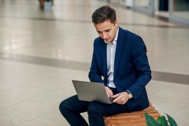 Jeune Femme D'affaires Réussie Travaillant Sur Un Ordinateur Portable Assis Sur Un Banc Photo Premium