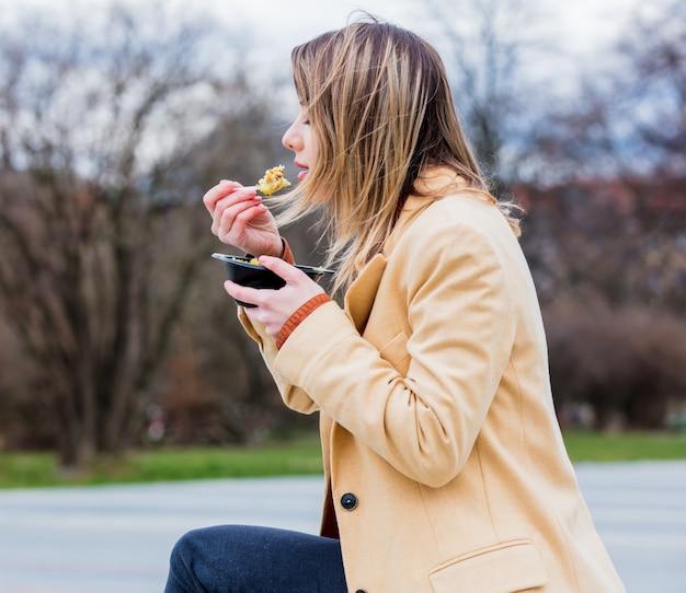 Jeune femme d'affaires avec une salade à la ville urbaine en plein air. Photo Premium