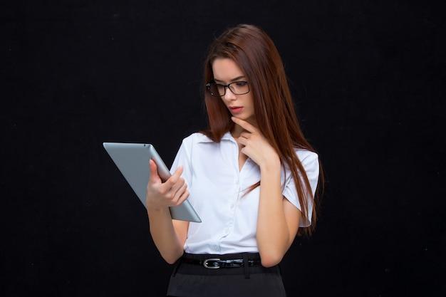 La Jeune Femme D'affaires Avec Tablette Sur Mur Noir Photo gratuit