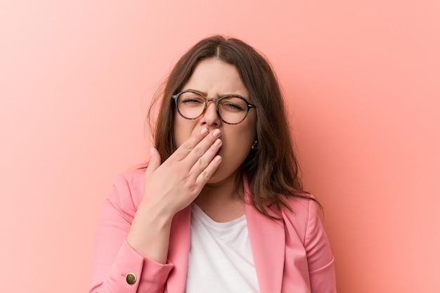 Jeune, femme d'affaires de taille plus caucasien, bâillement, montrant un geste fatigué, couvrant la bouche avec sa main. Photo Premium
