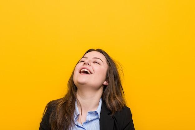 Jeune femme d'affaires de taille plus caucasien détendue et heureuse rire, cou tendu montrant les dents. Photo Premium