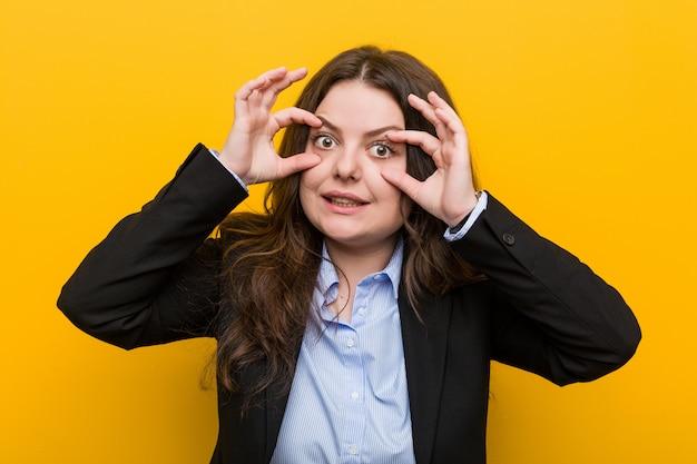 Jeune, femme d'affaires de taille plus caucasien, gardant les yeux ouverts pour trouver une occasion de réussir. Photo Premium