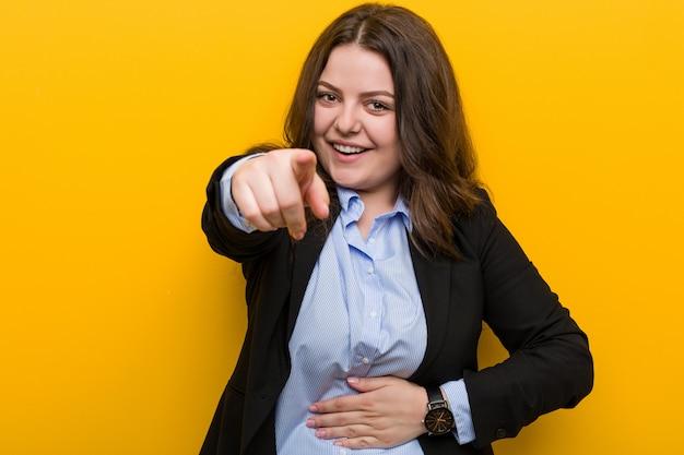 Jeune femme d'affaires de taille plus caucasien pointe avec le pouce loin, rire et insouciant. Photo Premium