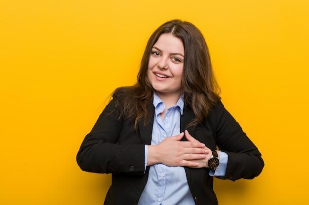 Jeune femme d'affaires de taille plus caucasienne a une expression amicale, appuyant de la paume sur la poitrine. amour . Photo Premium