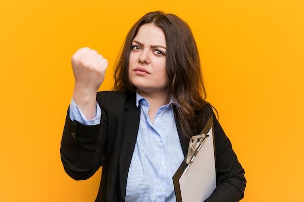 Jeune femme d'affaires de taille plus curvy holdingclipboard montrant le poing, expression faciale agressive. Photo Premium
