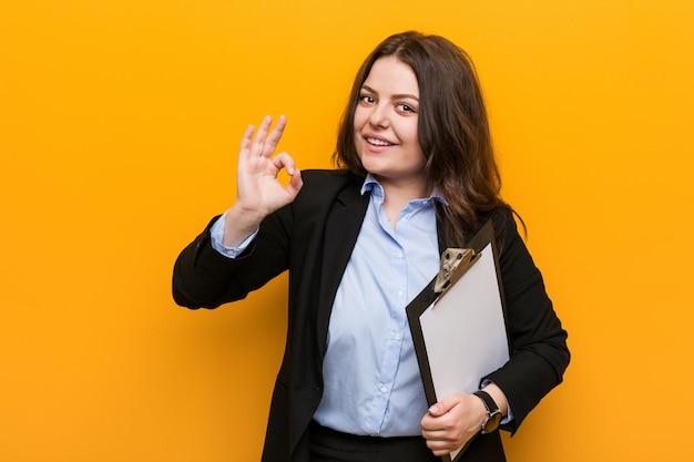 Jeune femme d'affaires de taille plus curvy tenant un presse-papiers gai et confiant montrant le geste correct. Photo Premium