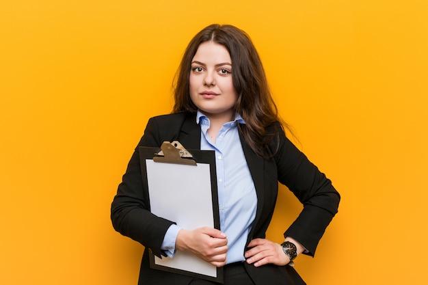 Jeune femme d'affaires de taille plus curvy tenant un presse-papiers souriant confiant avec les bras croisés. Photo Premium