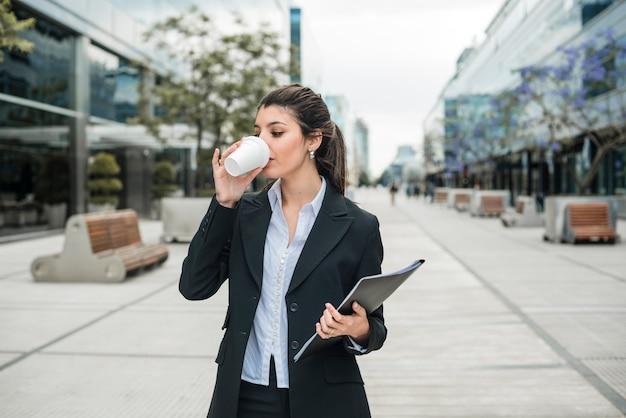 Jeune, femme affaires, tenue, dossier, main, boire, café, à, campus affaires Photo gratuit