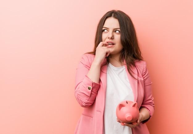 Jeune femme d'affaires tout en courbes de taille tenant une tirelire détendue pensant à quelque chose en regardant une copie. Photo Premium