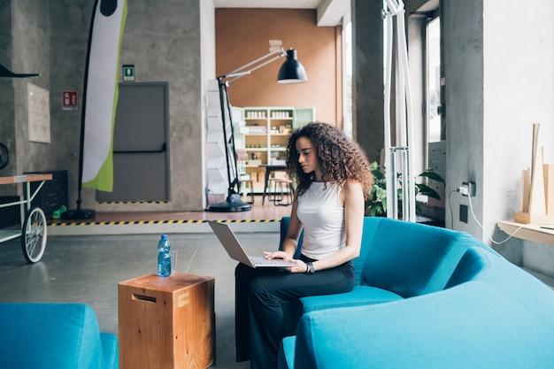Jeune femme d'affaires travaillant et assis avec un ordinateur portable dans un bureau moderne Photo Premium