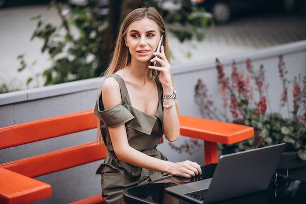 Jeune femme d'affaires travaillant sur un ordinateur portable à l'extérieur dans un café Photo gratuit