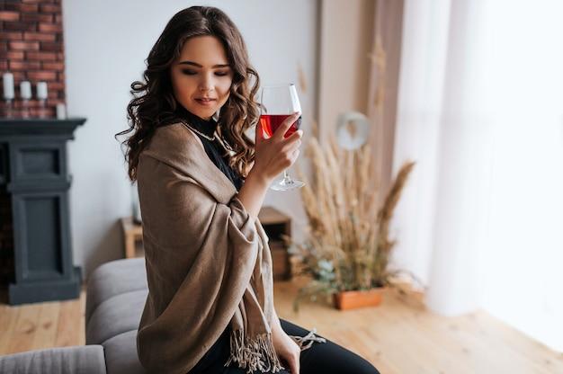 Jeune Femme D'affaires Travaille à La Maison. Tenez Un Verre De Vin Rouge à La Main. Beau Modèle En Robe De Soirée à La Fenêtre. Seul Dans La Chambre. Photo Premium