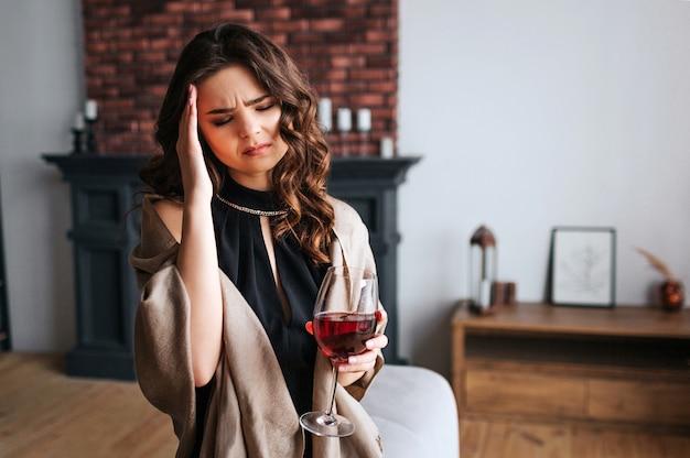 Jeune Femme D'affaires Travaille à La Maison. Tenez-vous Dans Le Salon Avec Un Verre De Vin Rouge à La Main. Mal De Crâne. Seul. Portez Une Robe Noire Et Un Châle Marron. Photo Premium