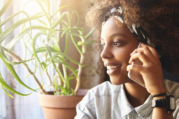 Jeune Femme Africaine Aux Cheveux Bouclés Parler Au Téléphone Photo gratuit