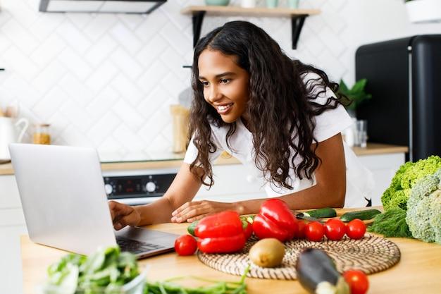 Jeune Femme Africaine Tape Quelque Chose Dans Un Ordinateur Portable Sur Un Bureau De Cuisine Avec Des Légumes Photo gratuit