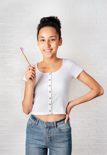 Jeune femme africaine tenant une brosse à dents en bambou sur fond blanc Photo Premium