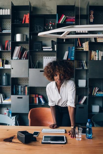 Jeune femme africaine travaillant dans le bureau de co-working et regardant la caméra Photo Premium