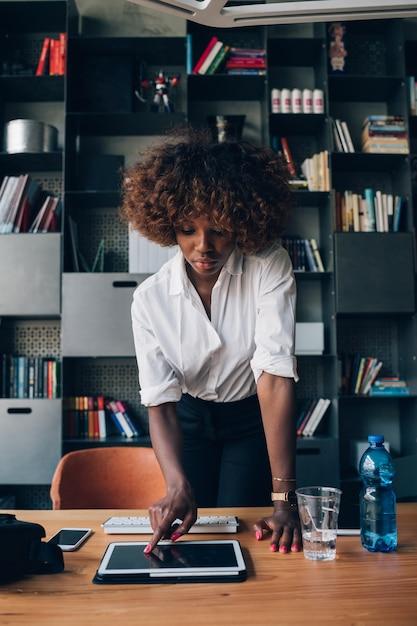 Jeune femme africaine travaillant avec tablette dans le bureau de co-working Photo Premium