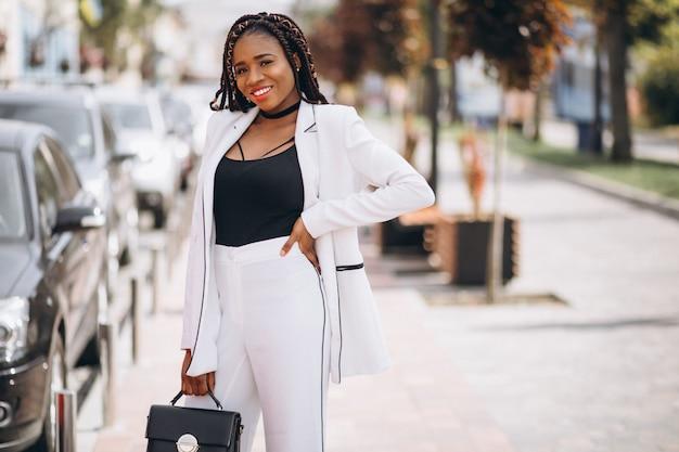 Jeune femme africaine vêtue d'un costume blanc en dehors de la rue Photo gratuit