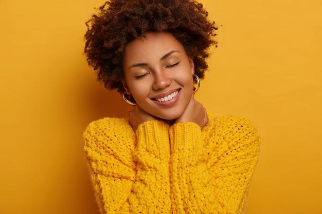 Jeune Femme Afro-américaine Bouclée Garde Les Yeux Fermés, Touche Le Cou Avec Les Deux Mains, Incline La Tête, Porte Un Pull Jaune Tricoté, Pose à L'intérieur. Photo gratuit