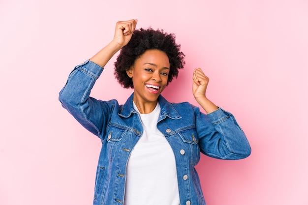 Jeune Femme Afro-américaine Contre Un Fond Rose Isolé Célébrant Une Journée Spéciale, Saute Et Lève Les Bras Avec énergie. Photo Premium