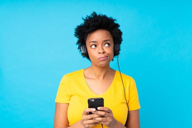 Jeune femme afro-américaine, écouter de la musique avec un mobile sur un mur bleu isolé Photo Premium
