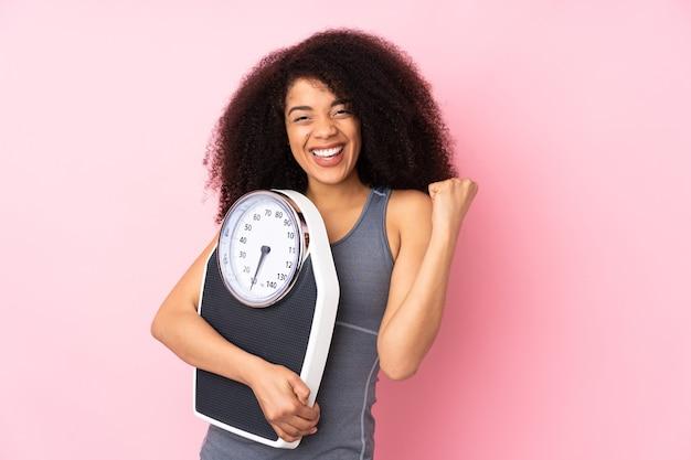 Jeune Femme Afro-américaine Isolée Sur Rose Avec Machine De Pesée Et Faisant Le Geste De La Victoire Photo Premium
