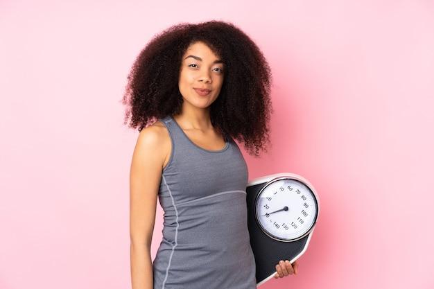 Jeune Femme Afro-américaine Isolée Sur Rose Avec Peseuse Photo Premium