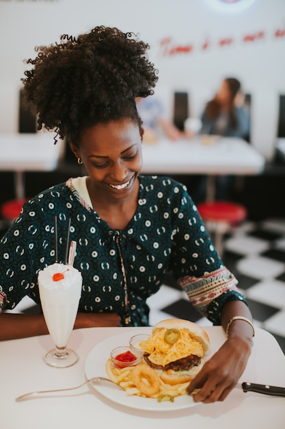 Jeune femme afro-américaine manger dans le diner Photo Premium