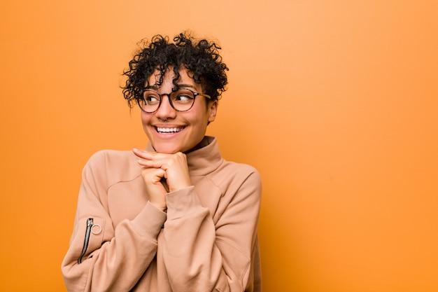 Jeune Femme Afro-américaine Mixte Contre Un Mur Brun Garde Les Mains Sous Le Menton, Regarde Joyeusement De Côté. Photo Premium