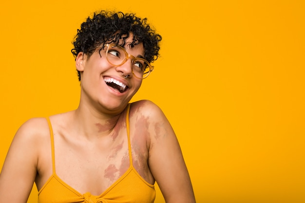 Jeune Femme Afro-américaine Avec La Tache De Naissance De La Peau Rit Joyeusement Et S'amuse En Gardant Les Mains Sur Le Ventre. Photo Premium
