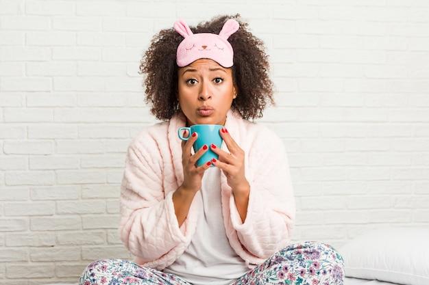 Jeune femme afro-américaine tenant une tasse sur le lit Photo Premium