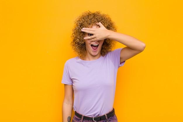Jeune Femme Afro à Choqué, Effrayé Ou Terrifié, Couvrant Le Visage Avec La Main Et Furtivement Entre Les Doigts Contre Le Mur Orange Photo Premium