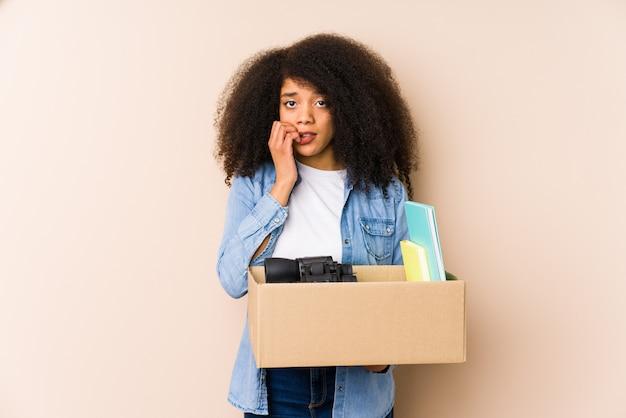 Jeune Femme Afro Déménageant Isolée Jeune Femme Afro Se Rongeant Les Ongles, Nerveuse Et Très Anxieuse. Photo Premium