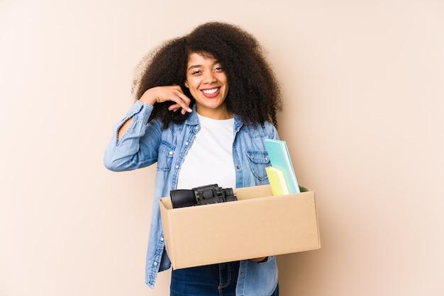 Jeune Femme Afro Déménageant à La Maison Isolée Jeune Femme Afro Montrant Un Geste D'appel De Téléphone Mobile Avec Les Doigts. Photo Premium