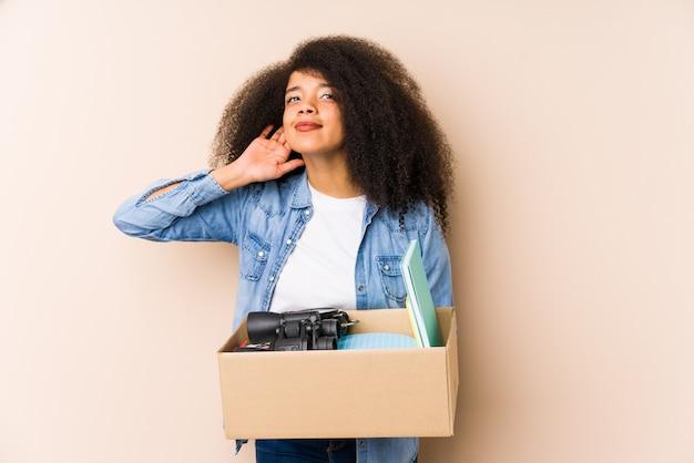 Jeune Femme Afro Se Déplaçant à La Maison Isolée Jeune Femme Afro Essayant D'écouter Un Potin. Photo Premium