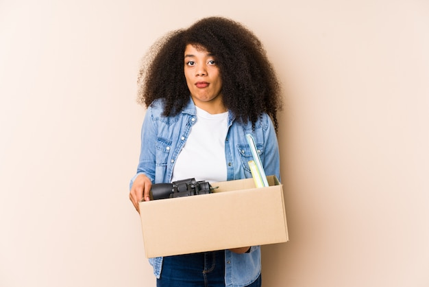 Jeune Femme Afro Se Déplaçant à La Maison Isolée Jeune Femme Afro Hausse Les épaules Et Les Yeux Ouverts Confus. Photo Premium